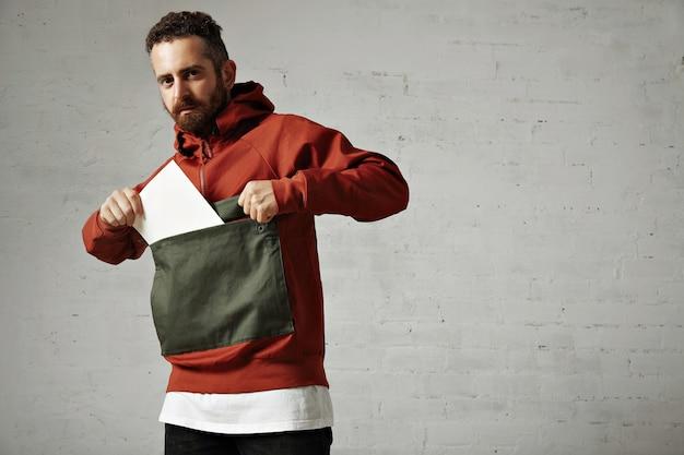 Attraktives männliches modell, das ein leeres weißes blatt papier aus der vordertasche seines roten und grauen parkas auf weiß nimmt
