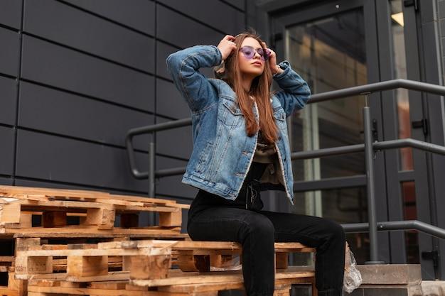 Attraktives modell der jungen frau in stilvoller kleidung zieht militärkapuze an. trendiges hipster-mädchen in violetter trendiger brille in jeansjacke, die auf vintage-holzpaletten in der nähe des grauen gebäudes in der stadt posiert.