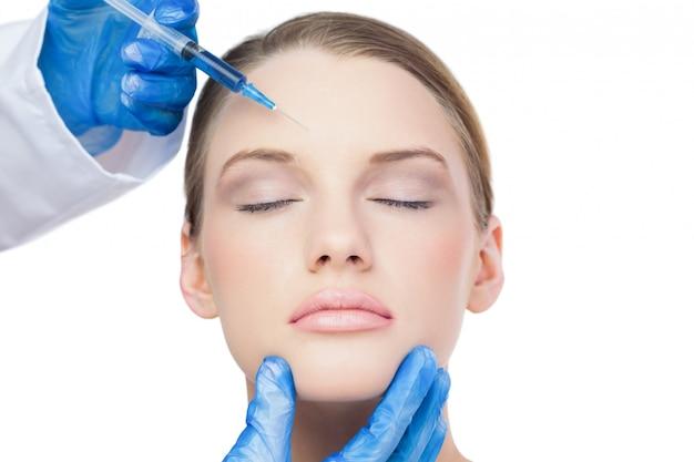 Attraktives modell des inhalts, das botox einspritzung auf die stirn hat
