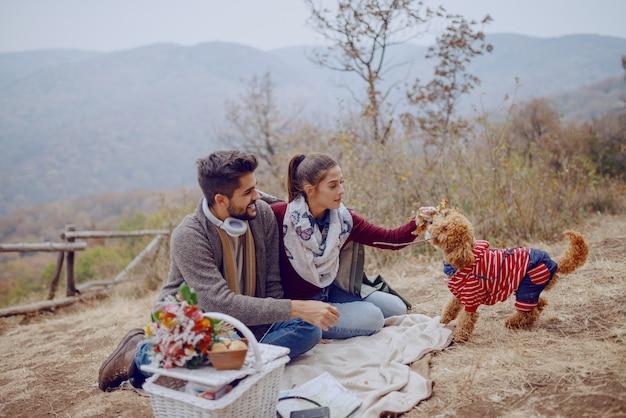 Attraktives multikulturelles paar, das auf decke sitzt und mit ihrem hund spielt. picknick am herbstkonzept.