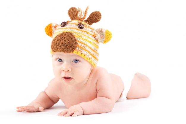 Attraktives nettes baby im rotwildkostüm liegt auf bauch