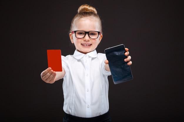 Attraktives nettes junges mädchen im weißen hemd und in der schwarzen hose halten rote karte und zeigt das telefon