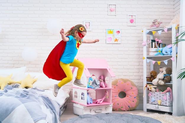 Attraktives nettes kleines mädchen springt vom bett, um zu fliegen, wenn sie superheld spielt
