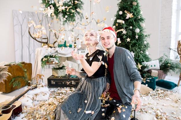 Attraktives paar, das feiertage zu hause feiert, trinkt champagner und wirft konfetti