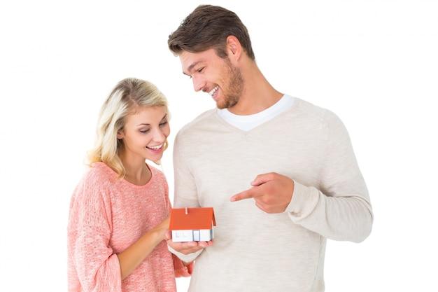 Attraktives paar, das miniaturhausmodell hält