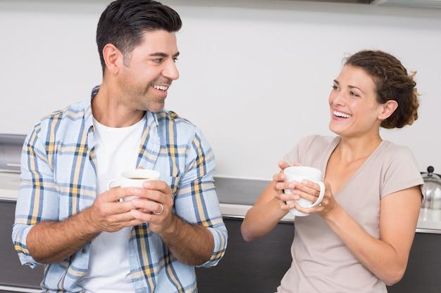 Attraktives paar, das sitzt, kaffee zusammen trinkend und lachend