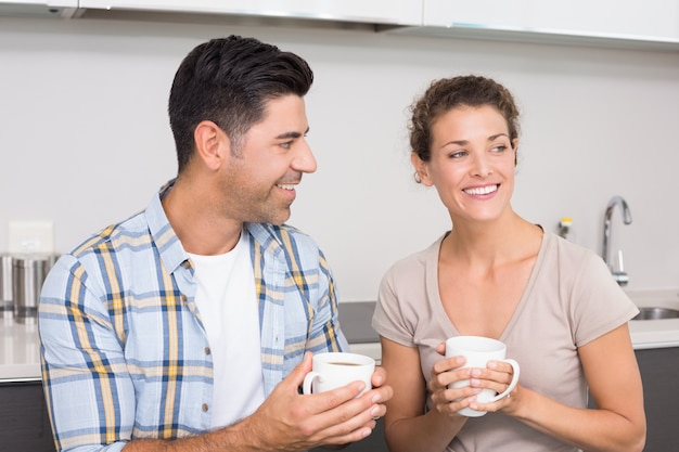 Attraktives paar, das sitzt, kaffee zusammen trinkend