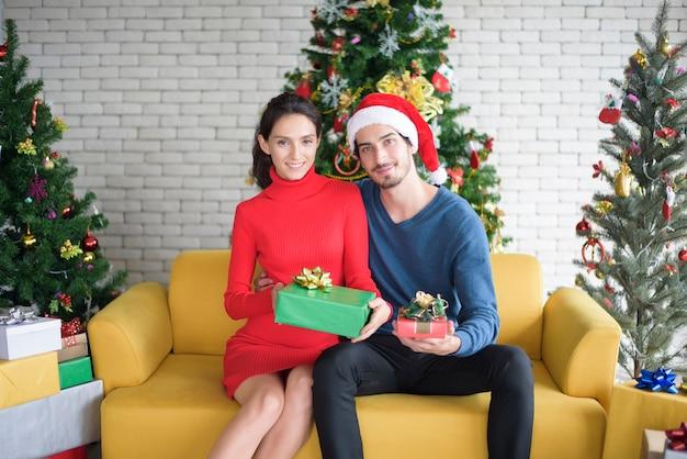 Attraktives paar, das weihnachten zu hause feiert