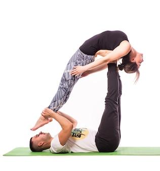 Attraktives paar, das zusammen yoga auf weißem hintergrund tut
