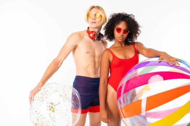 Attraktives paar europäischer mann und afrikanisches mädchen in badeanzügen mit sonnenbrille und kopfhörern gehen zum strand schwimmen auf schwimmmatratzen