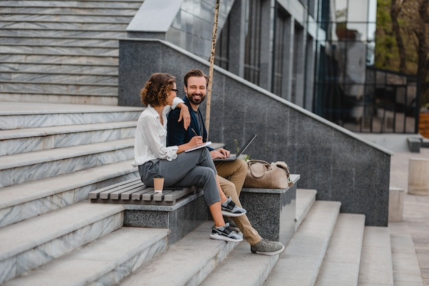 Attraktives paar von mann und frau, die auf treppen im städtischen stadtzentrum sitzen
