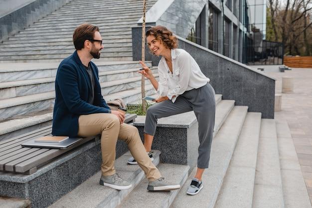 Attraktives paar von mann und frau, die im städtischen stadtzentrum sprechen und diskutieren