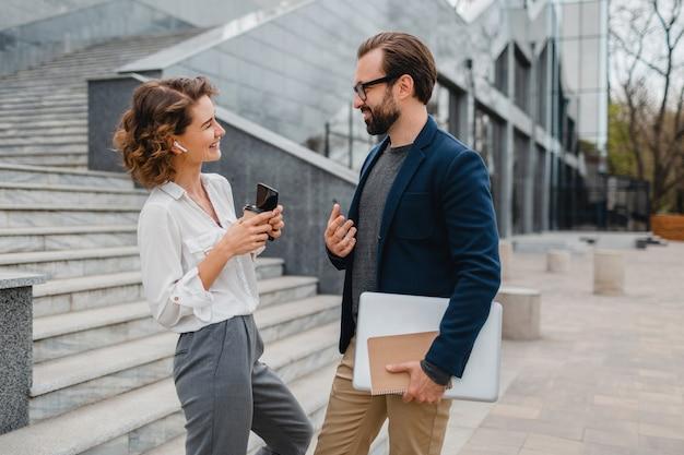 Attraktives paar von mann und frau, die im städtischen stadtzentrum sprechen