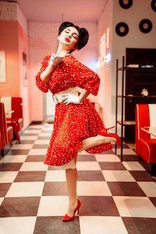 Attraktives pin-up-girl mit hellem make-up sendet luftkuss, vintage-café-interieur