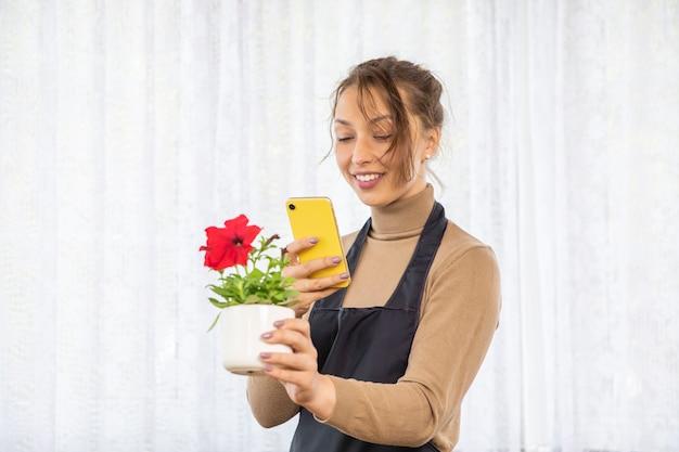 Attraktives positives freudiges mädchen, das bilder der blume im topf nach dem pflanzen macht