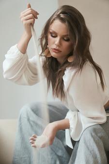 Attraktives professionelles model mit trendigem make-up und frisur sieht in weißer bluse und grauer hose sehr stylisch aus, während es meersand von einer hand in die andere gießt. mode sieht aus. modellierungskonzept