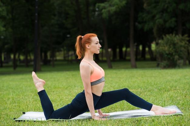 Attraktives rothaariges mädchen, das yoga praktiziert, während es auf einer matte auf dem gras im park sitzt
