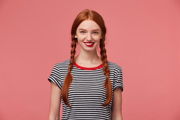 Attraktives schönes herzerwärmendes hübsches rothaariges mädchen mit roten lippen, zwei zöpfen, charmantes lächeln, zeigt weiße gesunde zähne, gekleidet in abgestreiftem t-shirt, isoliert