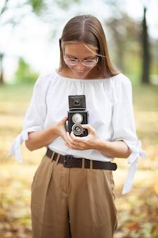 Attraktives schönes junges mädchen, das retro vintage doppellinsenreflexionskamera im herbstpark hält