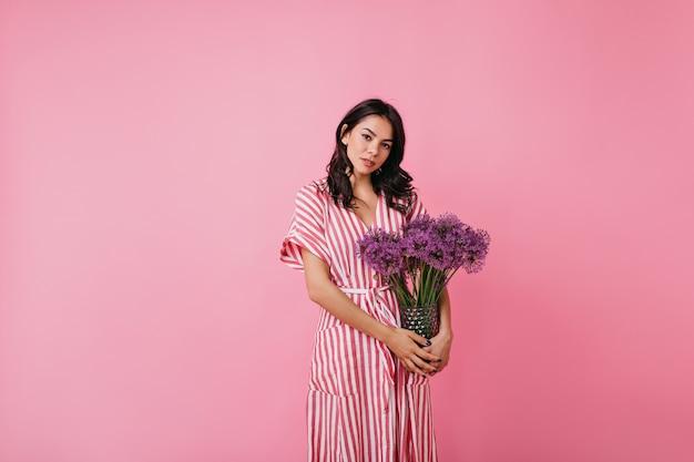 Attraktives schönes mädchen im gestreiften kleid, das mit lila blumen aufwirft. brünette sieht romantisch aus.