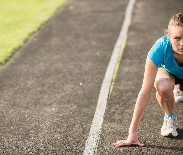 Attraktives sportliches mädchen bereit, sprint laufen zu lassen.