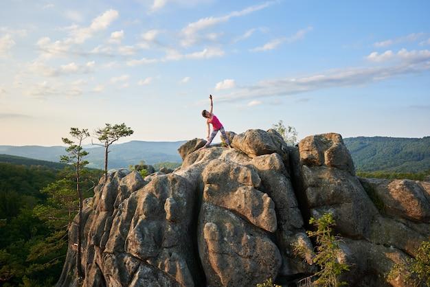 Attraktives sportliches mädchen, das komplizierte yogaübungen auf dem riesigen steinhaufen auf grünen bergen und klarem blauem himmel tut. klettern, tourismus, fitness und gesunder lebensstil.