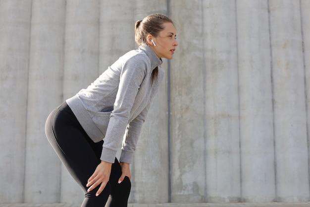 Attraktives sportliches mädchen der jungen fitness, das sich nach intensivem abendlauf im freien in der stadt ausruht.