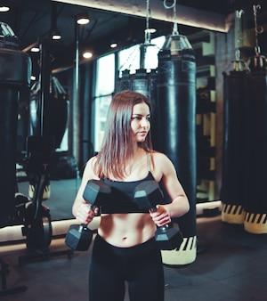 Attraktives sportliches mädchen in sportbekleidung hält hanteln in ihren händen und trainiert bizeps in der boxhalle.