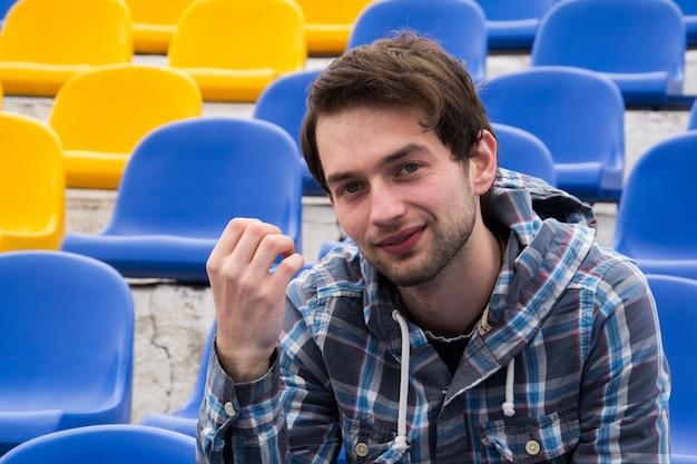 Attraktives sportliches modell des jungen mannes im blauen hemd, das auf blauen stadionsitzen nach dem training anstarrt entlang des feldes sitzt