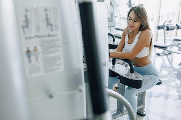 Attraktives sportmädchen, das auf dem simulator ruht und nett lächelt.