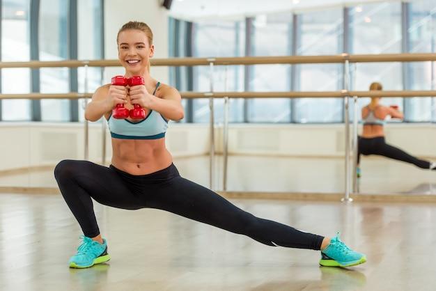 Attraktives sportmädchen, das front lächelt und betrachtet.
