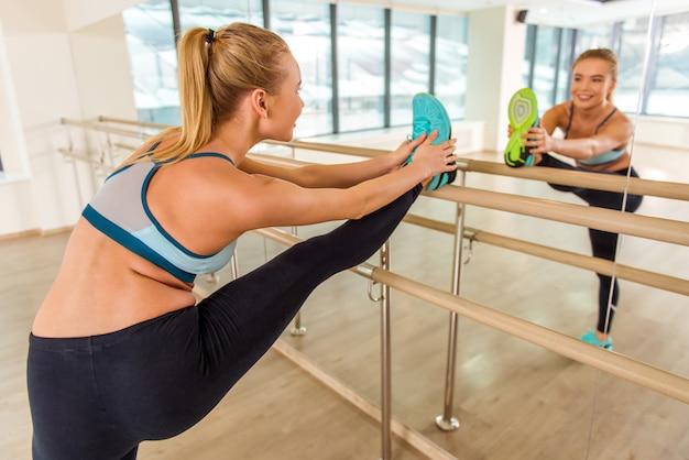 Attraktives sportmädchen, das im spiegel lächelt und schaut.