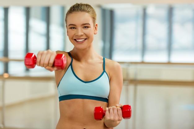 Attraktives sportmädchen, das kamera lächelt und betrachtet.