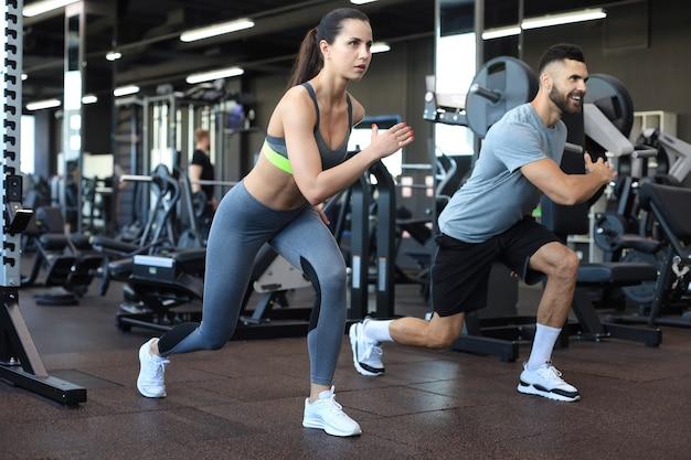 Attraktives sportpaar, das fitness im fitnessstudio macht.