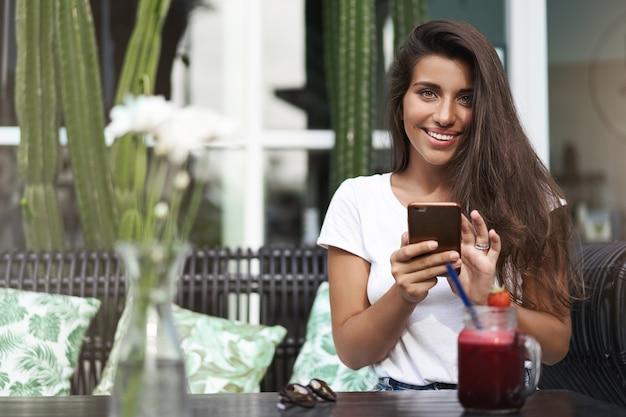 Attraktives stilvolles gebräuntes mädchen, das taxi anruft, verwenden smartphone-app o