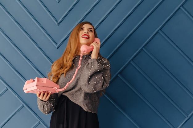Attraktives stilvolles junges mädchen mit retro- rosa telefon auf aquahintergrundgefühlen