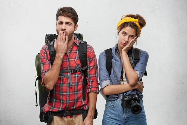 Attraktives stilvolles junges paar europäischer reisender, die sich gelangweilt oder müde fühlen: unrasierter mann, der beim gähnen den mund bedeckt, seine freundin, die kamera mit gelangweiltem desinteressiertem ausdruck betrachtet