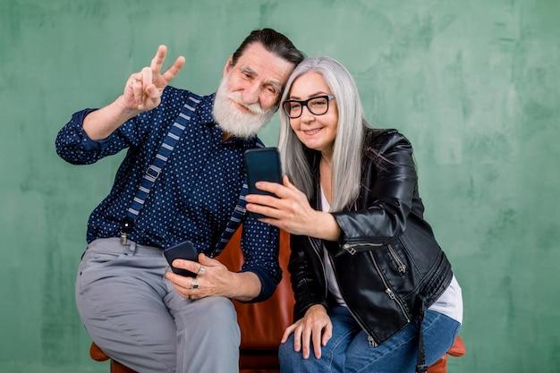 Attraktives stilvolles paar, bärtiger mann und grauhaarige dame, die zusammen auf dem roten stuhl sitzen und die telefonkamera zum fotografieren und lächeln verwenden