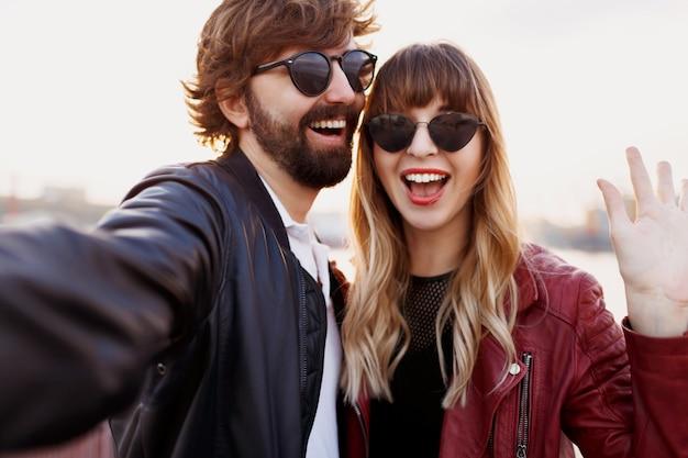 Attraktives stilvolles paar in der liebe, die im freien aufwirft, umarmt und auf kai geht. weiche abendfarben. modischer look. trendige sonnenbrille. mann und frau peinlich.