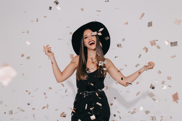 Attraktives stilvolles weibliches modell im hexenkostüm, das für halloween-partei auf isolierter wand mit konfetti-tanz vorbereitet, spaß hat, lächelt. geburtstag, feiertag