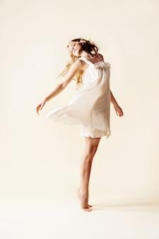 Attraktives tanzen der jungen frau, heller hintergrund des studios.