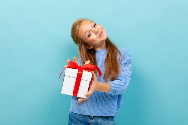 Attraktives teenager-mädchen, das ein geschenk mit einem roten band in ihren händen auf einem hellblauen hintergrund hält