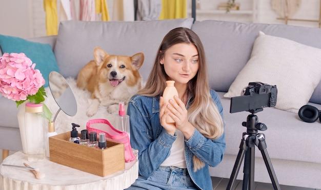 Attraktives teenager-mädchen mit ihrem niedlichen hund beim vlogging beim make-up.young-mädchen, das ihr beauty-videoblog schießt. junges mädchen führt beim bloggen fernunterricht zum make-up durch.