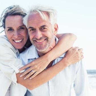Attraktives verheiratetes paar, das am strand an einem sonnigen tag aufwirft