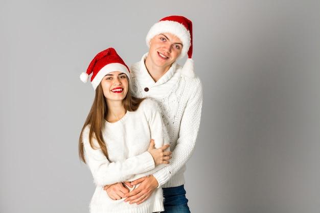 Attraktives verliebtes paar feiert weihnachten und hat spaß in weihnachtsmützen im studio auf grauem hintergrund