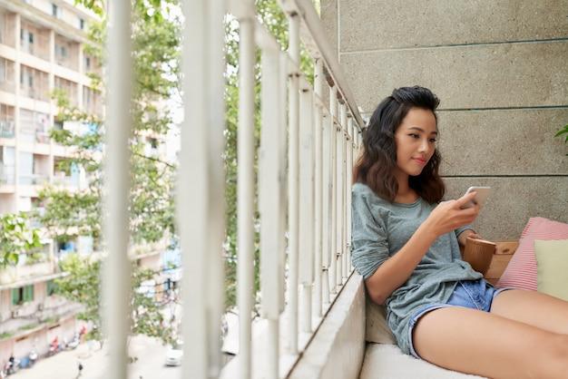 Attraktives vietnamesisches mädchen, das tee auf balkon simst und trinkt