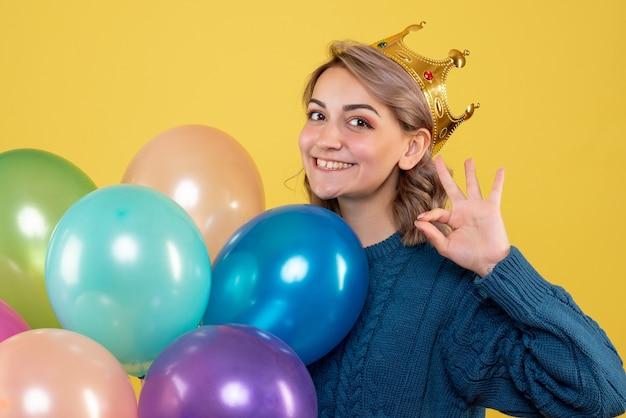 Attraktives weibchen mit bunten luftballons in der krone auf gelb