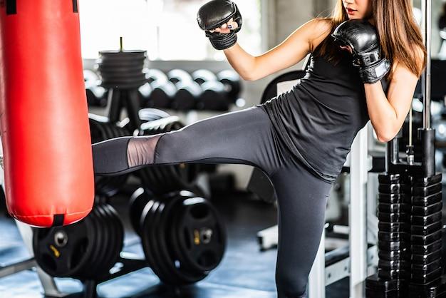 Attraktives weibliches boxertraining mit kickboxen im fitnessstudio mit schwarzen handschuhen.