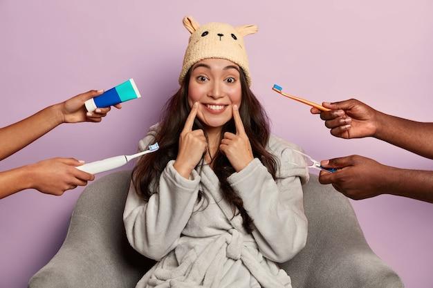 Attraktives weibliches modell putzt regelmäßig zähne, trägt lustigen haushut und bademantel