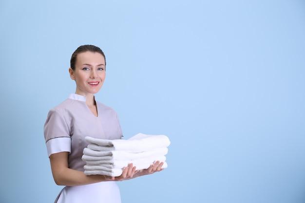 Attraktives zimmermädchen, das einen haufen sauberer handtücher auf farbigem hintergrund hält